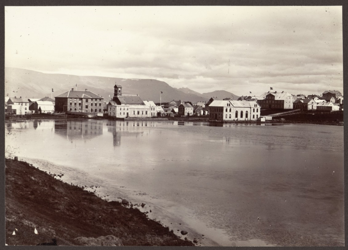 Reykjavík from the Tjörn [the Tarn, or Pond], ca. 1900. The view faces northeast and includes Parliament (center left), the national cathedral to its right and Menntaskólinn í Reykjavík, the country's main high school at the time (to the right, with flag flying). The mountain Esja rises in the background. From the Icelandic and Faroese Photographs of Frederick W.W. Howell.
